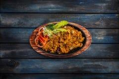 与paprica的被炖的圆白菜在平底锅有在土气样式的木背景 图库摄影
