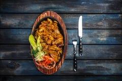 与paprica的被炖的圆白菜在平底锅有在土气样式的木背景 免版税库存图片