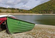 与Pebble海滩的迪梅尔塞,德国-湖岸,靠岸的绿色小船和树木繁茂的小山在距离 库存图片