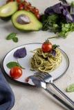 与pesto、草本和西红柿的意大利面团在白色板材 免版税库存照片