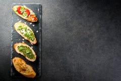 与pesto、巴马干酪、蕃茄和蓬蒿的Bruschetta 库存照片