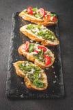 与pesto、巴马干酪、蕃茄和蓬蒿的Bruschetta 免版税库存图片
