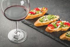 与pesto、巴马干酪、蕃茄和蓬蒿的Bruschetta 库存图片