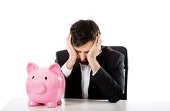与piggybank的商人由书桌 免版税库存图片