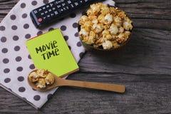 与popcord和遥控的电影放映时间词在木背景 免版税图库摄影