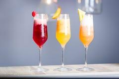 与Prosecco,三种类的五颜六色的夏天鸡尾酒水果鸡尾酒-莓、桃子和菠萝,水平的墙纸 图库摄影