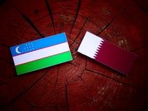 与Qatari旗子的乌兹别克斯坦旗子在被隔绝的树桩 图库摄影