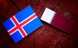 与Qatari旗子的冰岛旗子在被隔绝的树桩 免版税库存图片