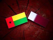 与Qatari旗子的几内亚比绍旗子在被隔绝的树桩 免版税库存照片