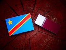与Qatari旗子的刚果民主共和国旗子在被隔绝的树桩 库存照片