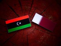 与Qatari旗子的利比亚旗子在被隔绝的树桩 免版税库存图片