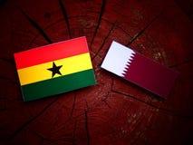 与Qatari旗子的加纳的旗子在被隔绝的树桩 库存照片