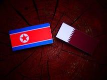 与Qatari旗子的北朝鲜的旗子在被隔绝的树桩 图库摄影