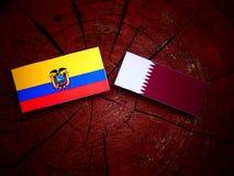 与Qatari旗子的厄瓜多尔旗子在被隔绝的树桩 库存图片