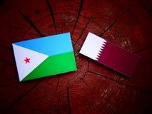 与Qatari旗子的吉布提旗子在被隔绝的树桩 免版税库存照片