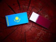 与Qatari旗子的哈萨克斯坦旗子在被隔绝的树桩 库存图片
