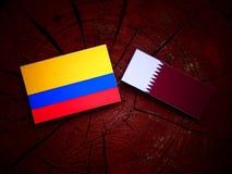 与Qatari旗子的哥伦比亚的旗子在被隔绝的树桩 免版税库存照片