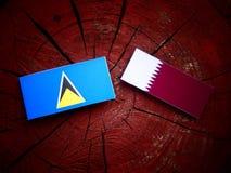 与Qatari旗子的圣卢西亚旗子在被隔绝的树桩 免版税图库摄影