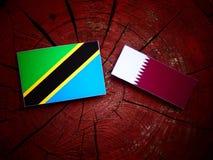 与Qatari旗子的坦桑尼亚的旗子在被隔绝的树桩 免版税库存图片