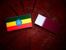 与Qatari旗子的埃赛俄比亚的旗子在被隔绝的树桩 库存照片