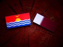 与Qatari旗子的基里巴斯旗子在被隔绝的树桩 免版税库存图片