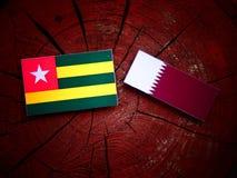 与Qatari旗子的多哥旗子在被隔绝的树桩 免版税库存照片