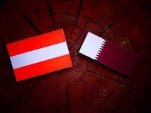 与Qatari旗子的奥地利旗子在被隔绝的树桩 免版税库存照片