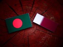 与Qatari旗子的孟加拉国旗子在被隔绝的树桩 库存图片
