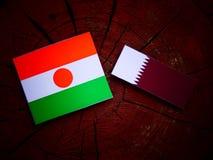 与Qatari旗子的尼日尔旗子在被隔绝的树桩 库存图片