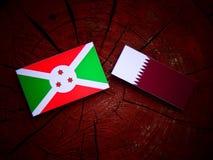 与Qatari旗子的布隆迪旗子在被隔绝的树桩 库存照片