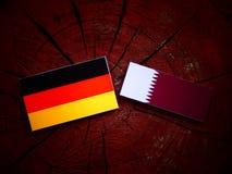 与Qatari旗子的德国旗子在被隔绝的树桩 库存照片