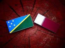 与Qatari旗子的所罗门群岛旗子在被隔绝的树桩 免版税库存图片