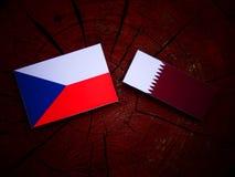 与Qatari旗子的捷克旗子在被隔绝的树桩 图库摄影