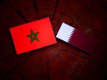 与Qatari旗子的摩洛哥旗子在被隔绝的树桩 图库摄影
