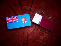 与Qatari旗子的斐济旗子在被隔绝的树桩 免版税库存照片