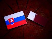 与Qatari旗子的斯洛伐克的旗子在被隔绝的树桩 库存图片