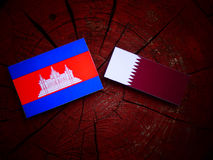与Qatari旗子的柬埔寨旗子在被隔绝的树桩 免版税库存图片