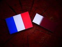 与Qatari旗子的法国旗子在被隔绝的树桩 库存图片
