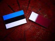 与Qatari旗子的爱沙尼亚语旗子在被隔绝的树桩 免版税图库摄影