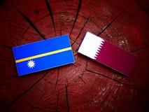 与Qatari旗子的瑙鲁旗子在被隔绝的树桩 免版税库存图片