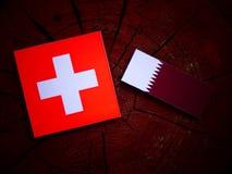 与Qatari旗子的瑞士旗子在被隔绝的树桩 库存照片