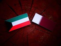 与Qatari旗子的科威特旗子在被隔绝的树桩 库存图片