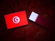 与Qatari旗子的突尼斯旗子在被隔绝的树桩 库存图片