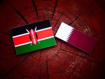与Qatari旗子的肯尼亚旗子在被隔绝的树桩 免版税图库摄影