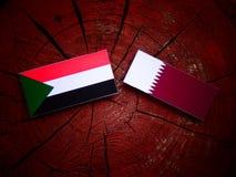 与Qatari旗子的苏丹旗子在被隔绝的树桩 免版税库存照片