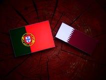 与Qatari旗子的葡萄牙旗子在被隔绝的树桩 库存图片