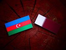 与Qatari旗子的阿塞拜疆旗子在被隔绝的树桩 免版税库存图片
