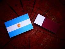 与Qatari旗子的阿根廷旗子在被隔绝的树桩 免版税图库摄影