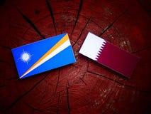 与Qatari旗子的马绍尔群岛旗子在被隔绝的树桩 免版税库存图片