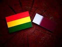 与Qatari旗子的玻利维亚的旗子在被隔绝的树桩 免版税库存图片